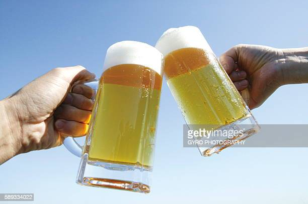 Hands toasting with glass of beer against blue sky, blue background