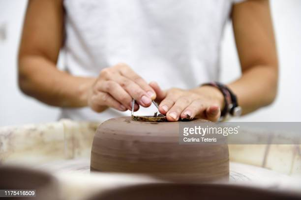 hands trimming clay on a potter's wheel - art and craft product stock pictures, royalty-free photos & images