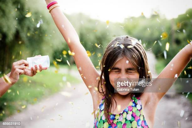 Hands Trowing Golden Confetti on a young girl