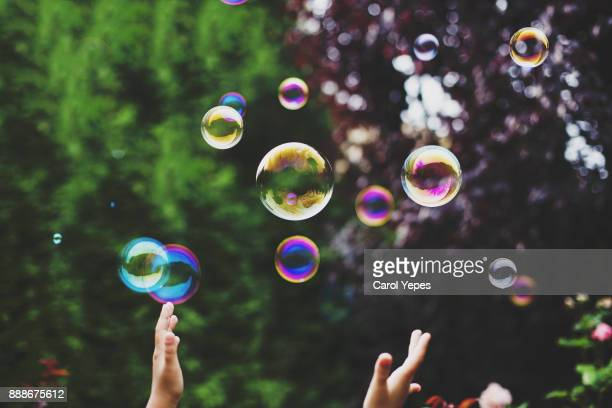 Hands trying to catch  soap bubbles