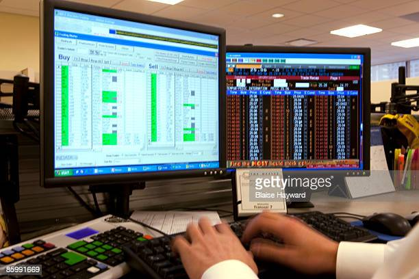 Hands typing at stock brokers desk