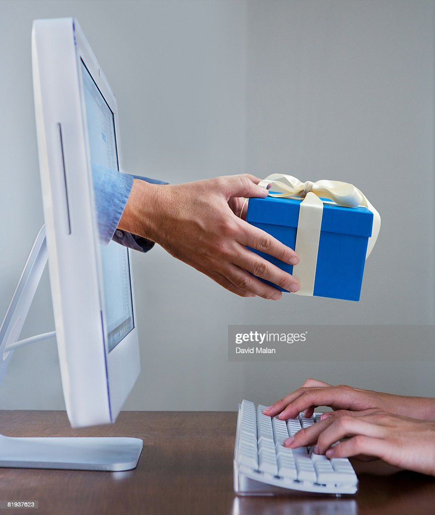 Hands typing on keyboard while a gift appears from a computer screen : Bildbanksbilder