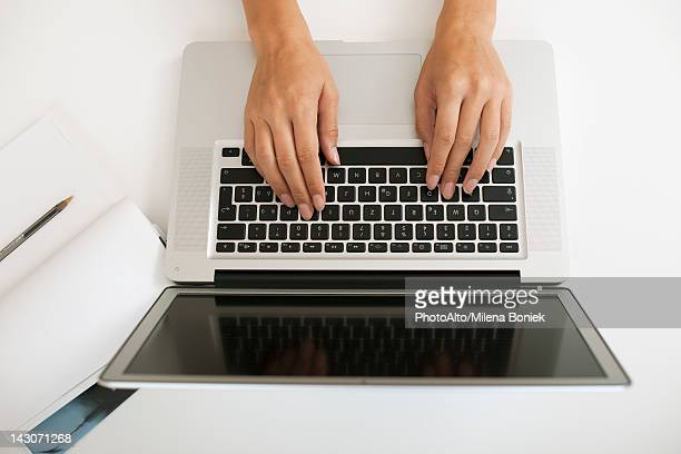 Hands typing on laptop computer, high angle view