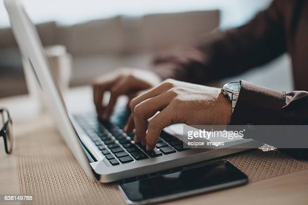 hands typing on laptop computer - man in office stock photos and pictures
