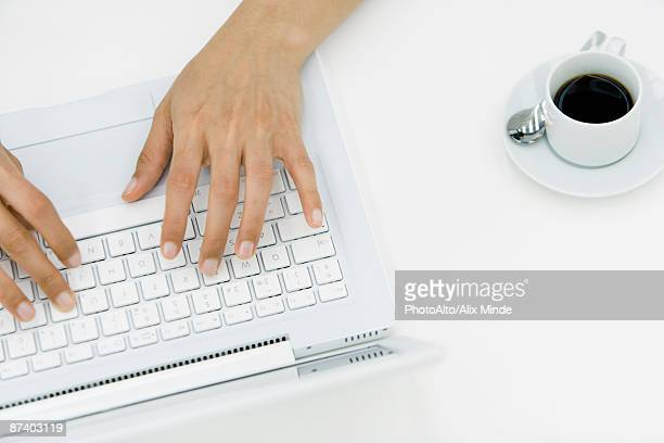 Hands typing on laptop, high angle view