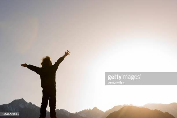 Manos arriba con éxito y alabanza en las montañas