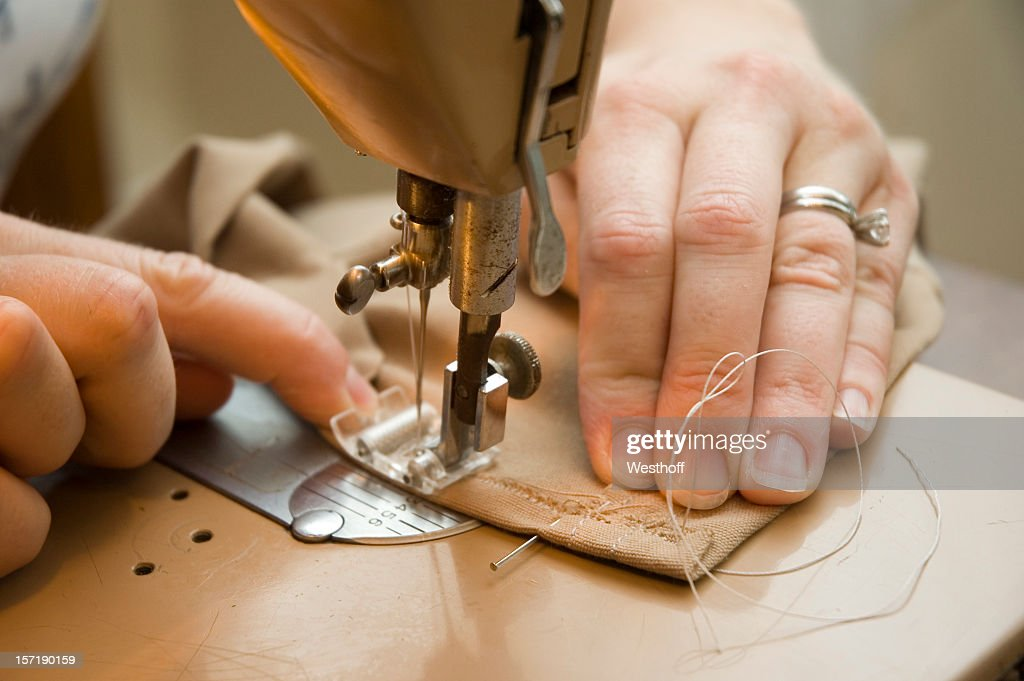 Hands using a sewing machine to sew brown material : Stock Photo