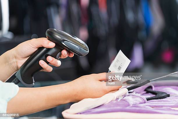 Hands using scanner to scan price tag in clothing store
