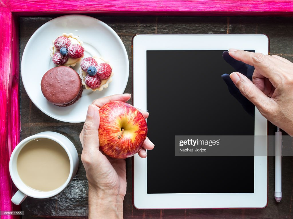 Hands using tablet computer over  wooden tray of light meal : Stock Photo