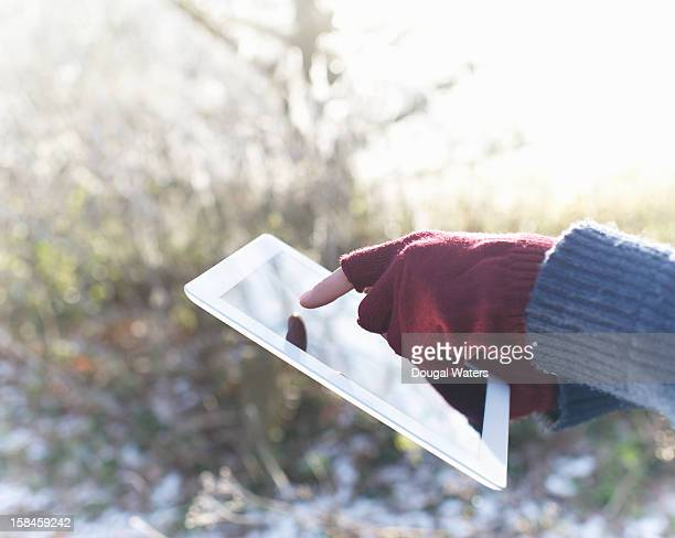 Hands using tablet on frosty morning.