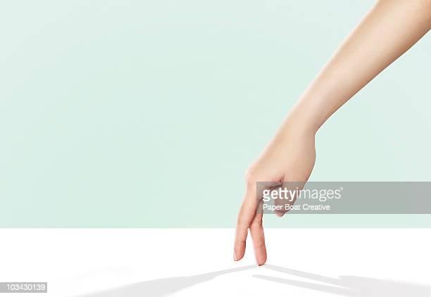 hands walking across a bright white surface - finger stock-fotos und bilder