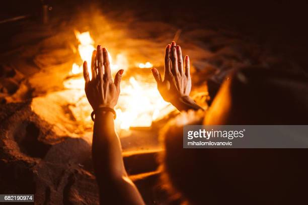 Hands warming up to fireplace
