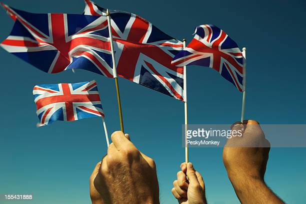hands wave union jack british flags blue sky - british flag stock photos and pictures