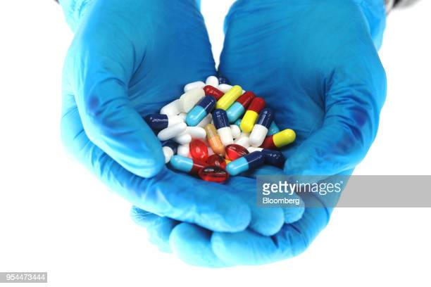 Hands wearing blue surgical gloves hold brightly coloured pharmaceutical medication including antibiotics paracetamol Ibuprofen and cold relief...