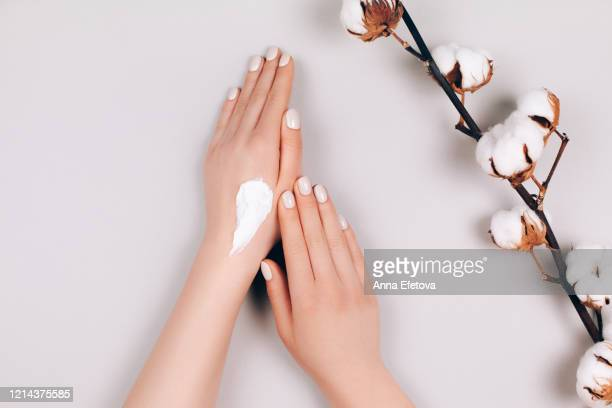 hands with a cotton branch - lichaamsverzorging en schoonheid stockfoto's en -beelden