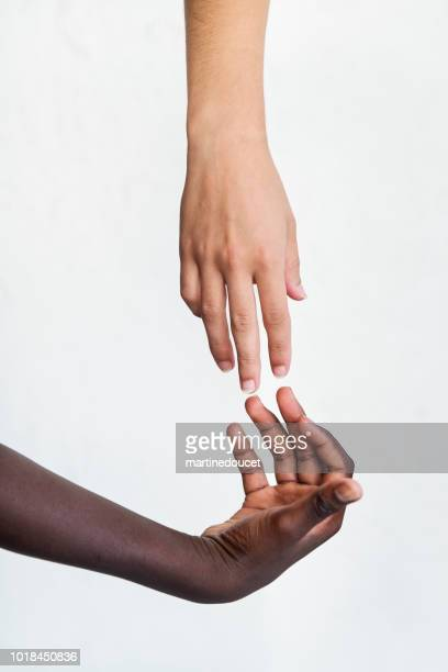 Hands with different skin colors on white background.