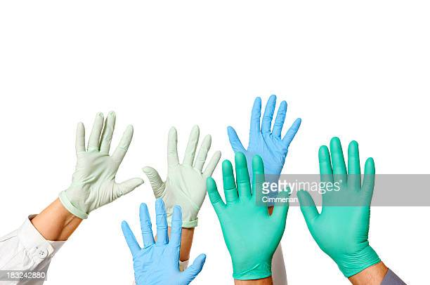 Hands with doctor rubber gloves in green, blue, and white