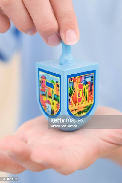 hands with dreidel - dreidel stock photos and pictures