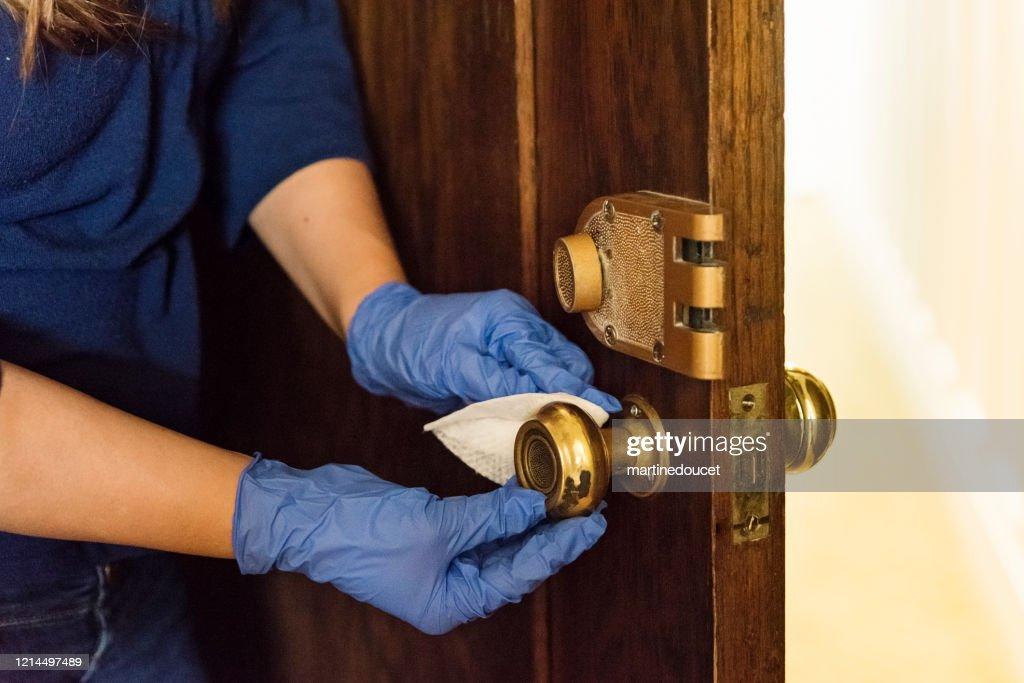 Hands with glove wiping doorknob on wooden door. : Stock Photo