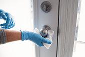 Hands with glove wiping doorknob.