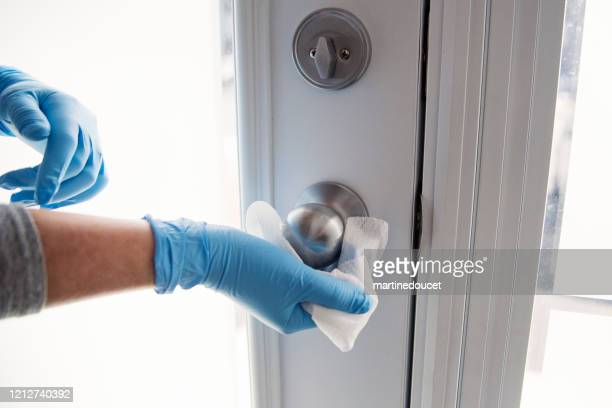 hands with glove wiping doorknob. - pathogen stock pictures, royalty-free photos & images