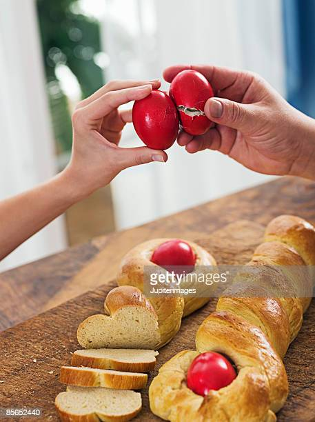 Hands with Greek Easter bread and eggs