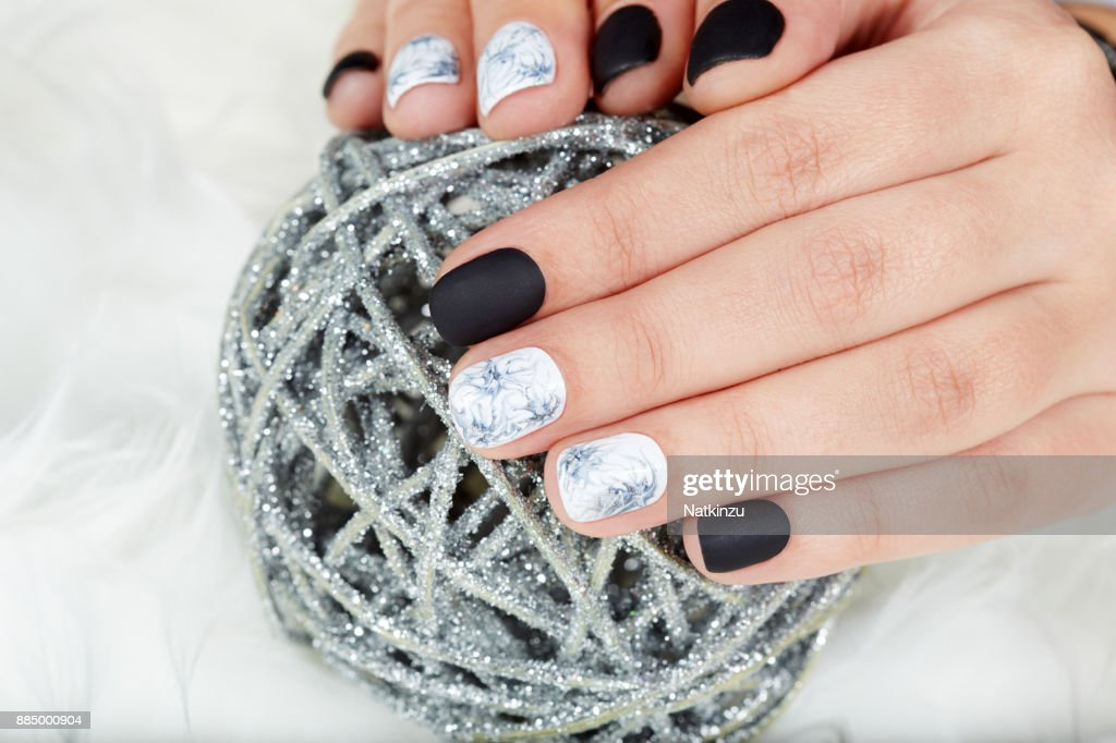 Hands with manicured nails colored with black and white nail polish : Stock Photo