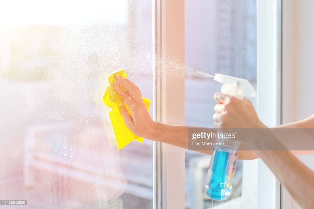 Hands with napkin cleaning window. Washing the glass on the windows with cleaning spray : Stock Photo