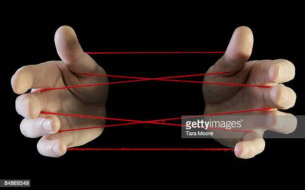 hands with red cats cradle