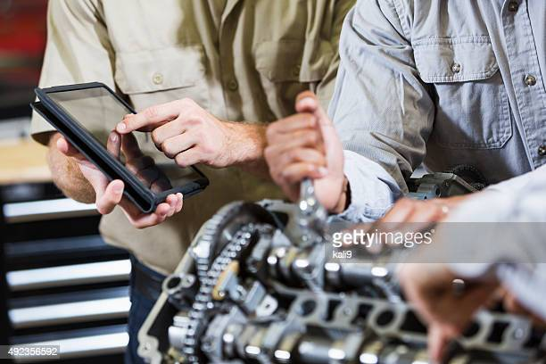 Hands working on car engine