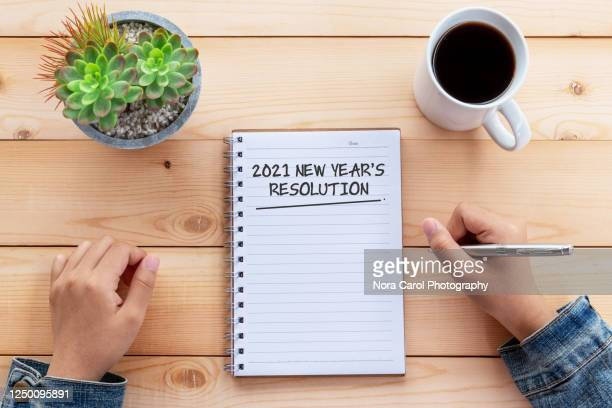 hands writing 2021 new year's resolution text on note pad on wood desk - new year stock pictures, royalty-free photos & images