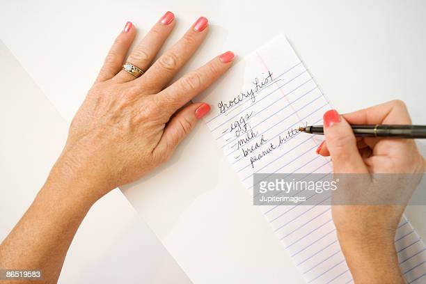 Hands writing grocery list