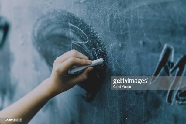 hands writing in chalkboard - bord bericht stockfoto's en -beelden