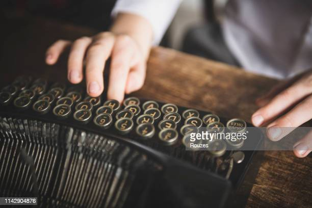 hands writing on a vintage typewriter. - authors foto e immagini stock