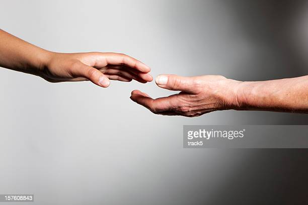 hands: young and old hands reaching out to each other - releasing stock pictures, royalty-free photos & images