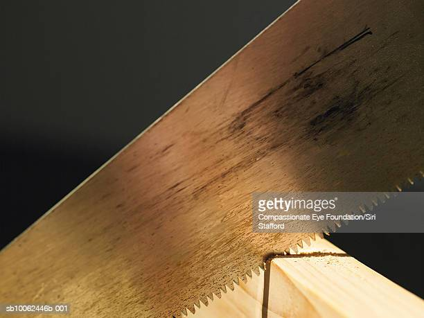 Handsaw cutting through block of wood, close-up