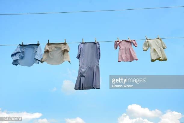 hand-sewn cotton amish dresses, shirts for children and adult hanging on a clothesline outdoors against the sky. - lancaster pennsylvania stock pictures, royalty-free photos & images
