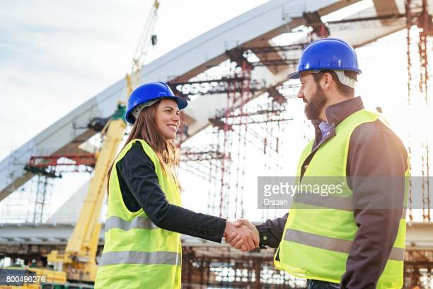 handshake after successful deal between consortium members - bridge built structure stock pictures, royalty-free photos & images