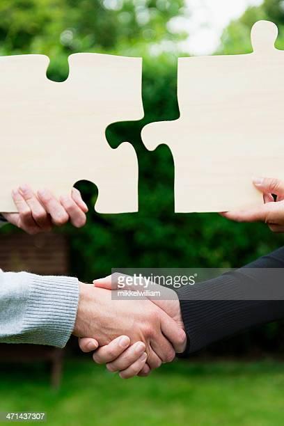 Hände schütteln und zwei puzzles Meeting