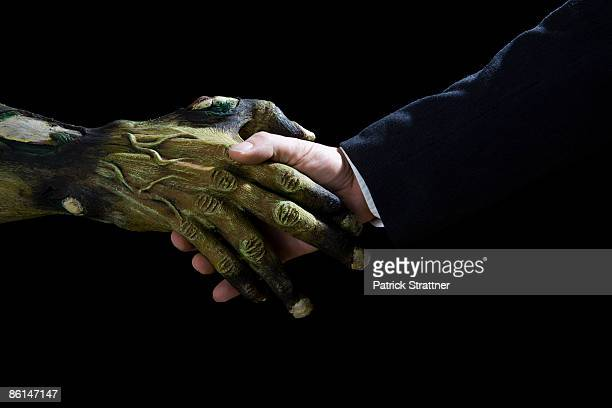 handshake between a monster and a businessman - scary monster ストックフォトと画像