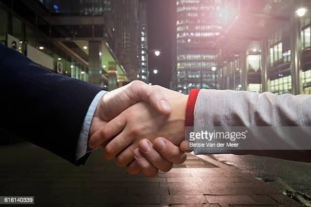 Handshake between businesspeople in city.