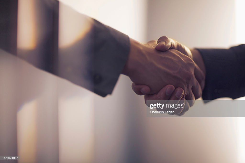 Handshake in contemporary office space : Stock Photo