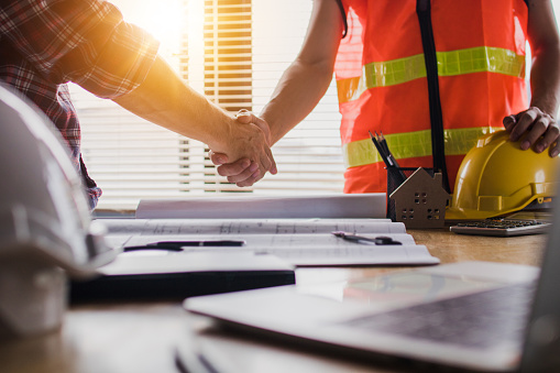 Handshake of two business man, after  architect working and planning blueprint, Engineering objects on workplace 1162145551