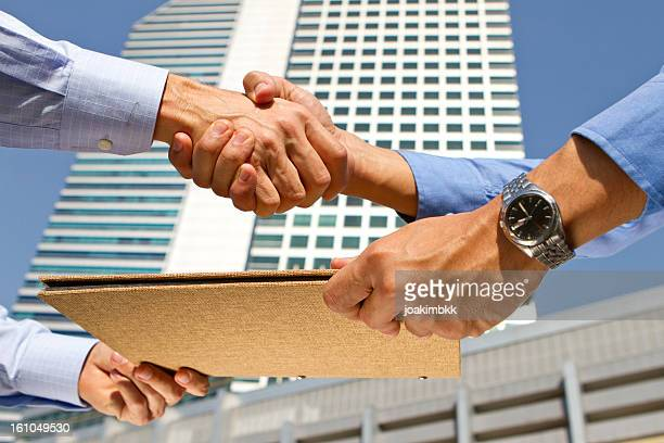 handshake over a business agreement in a financial district - human body part stock pictures, royalty-free photos & images