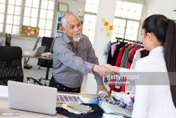aperto de mão com o novo assistente - vendedor de loja - fotografias e filmes do acervo