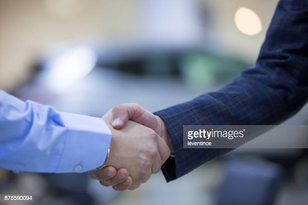 handshaking in a car showroom - salesman stock pictures, royalty-free photos & images