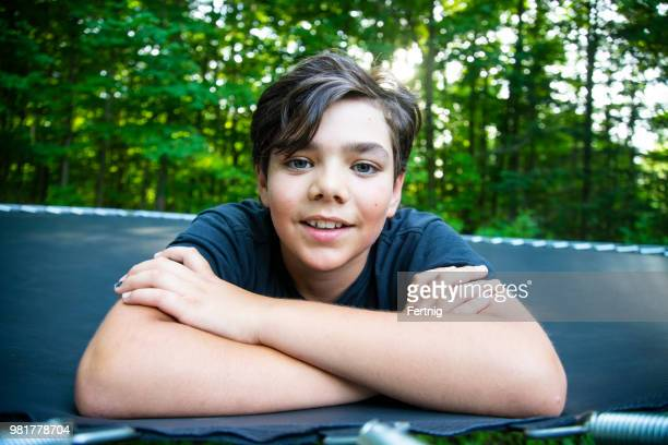 handsome 12-jarige op een trampoline - 12 13 jaar stockfoto's en -beelden