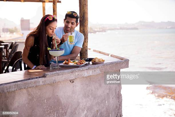 handsome 20's hispanic couple  in outdoor restaurant overlooking the bay - margarita beach stock photos and pictures