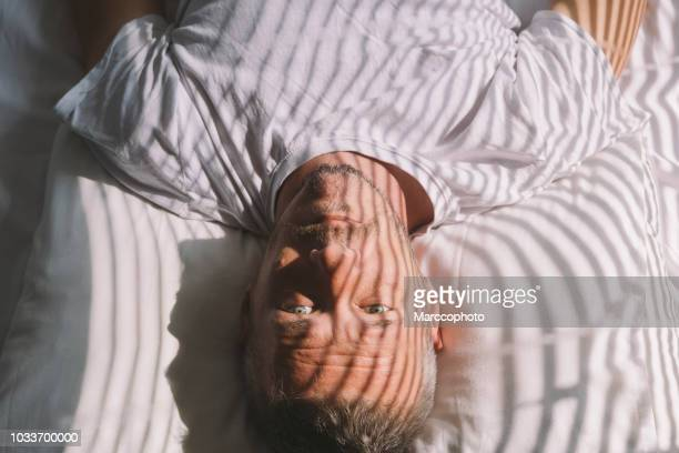 handsome adult man wakes up in the morning, lying on back, with sunlight illuminated him through window with blinds - lying down stock pictures, royalty-free photos & images
