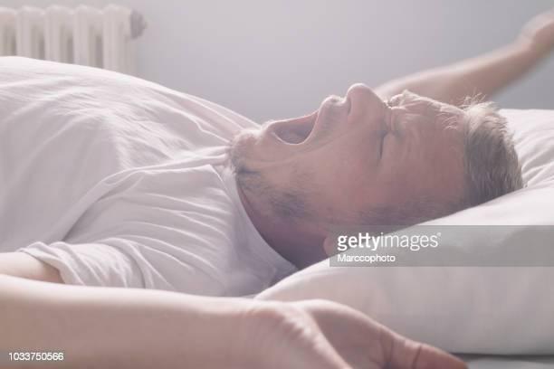 ハンサムな成人男性が目覚める朝は、あくびをして伸び、背中に横たわって - あくび ストックフォトと画像